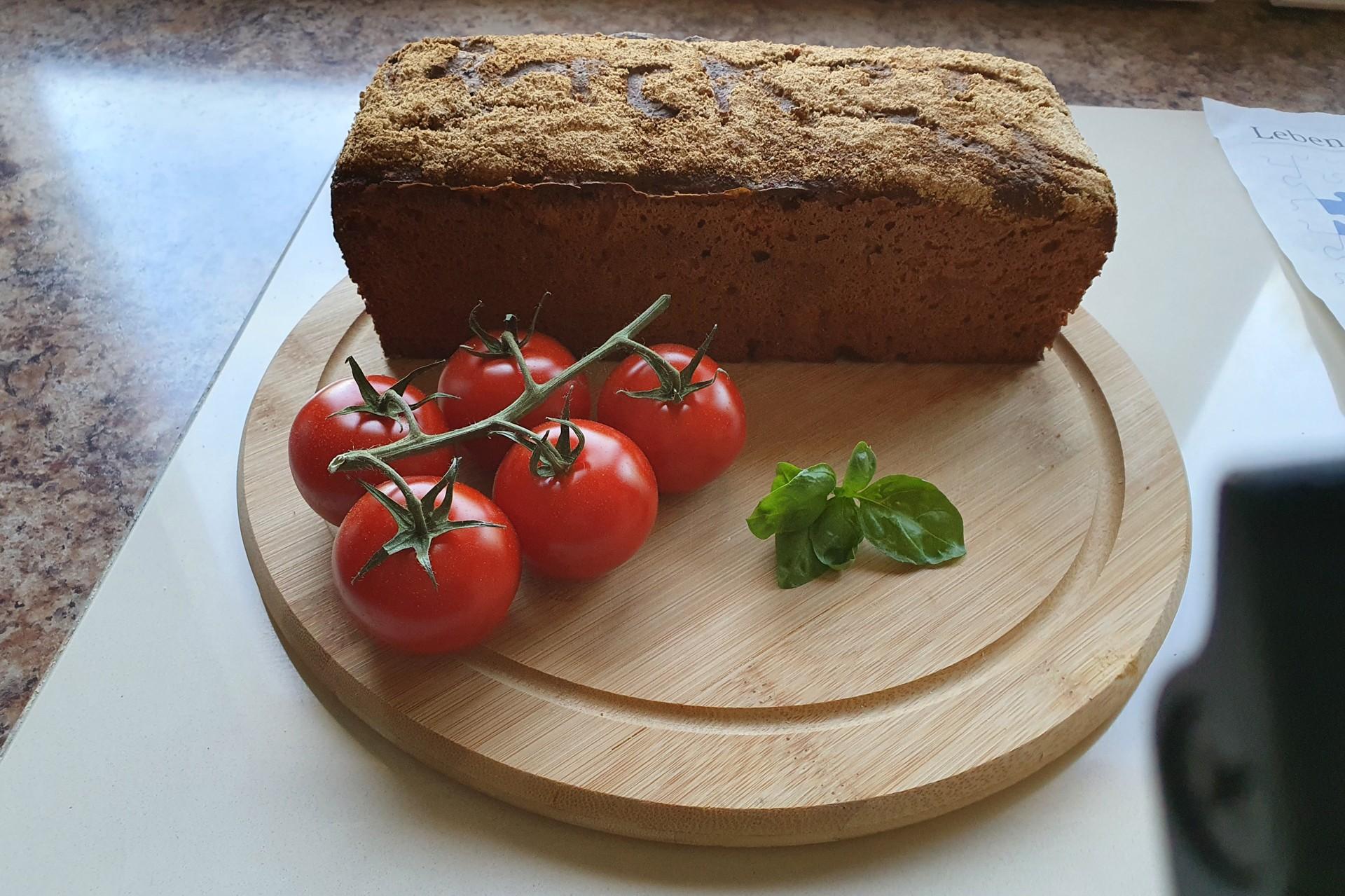 Kastenbrot mit Tomaten auf Holzbrett
